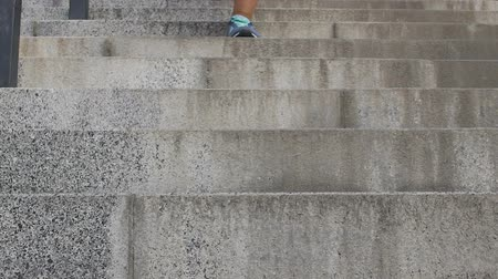run down : Legs of female student slowly running down stairs in university, end of classes