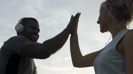 пять : Genuinely smiling male and female high five each other in slowmotion, happiness