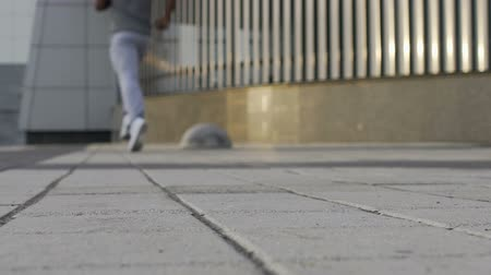 escuta : Out of focus man slowly running in background, metropolitan area, concrete Stock Footage