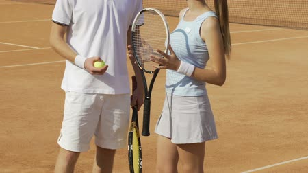 teniszütő : Man and woman in sportswear standing on tennis court and flirting, sports hobby