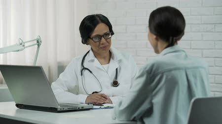 informar : Friendly doctor talking to patient, promising to help, informing good results