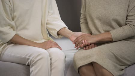restful : Young lady holding and stroking hand of senior woman, calming and supporting