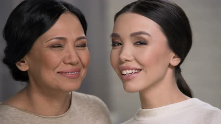 азиатский : Two smiling asian women looking at camera, mother and daughter faces closeup