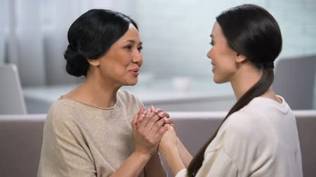 rejoice : Mother talking to daughter and holding her hands, giving advice, motherhood
