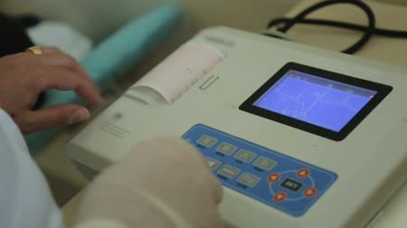 cardiologista : Female doctor printing out cardiogram paper result, heart attack, medical care Stock Footage