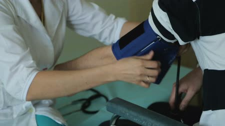 hemşirelik : Clinic worker putting blood pressure cuff on patient arm, sphygmomanometer Stok Video