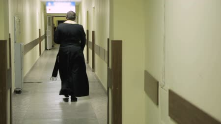 bible black : Priest back in black going along hospital corridor for dying patient confession
