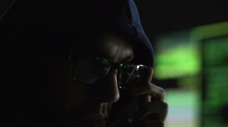 hacker computer : Programmer intently looking at monitor checking data, reflection in glasses