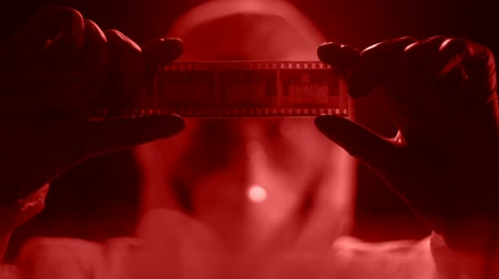 criminalist : Man in lab costume watching camera roll, developing photograph in red light