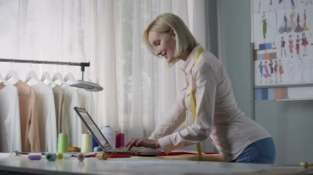 measure tape : Cheerful seamstress ordering color palette for her clothes collection online Stock Footage