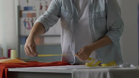 genişlik : Woman tailor measuring width of sewing dress, working in atelier, creativity