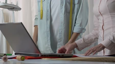 couturier : Designer and assistant looking cloth exhibition on laptop, discussing the shades