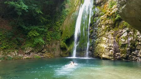 fröcskölés : Brave man swimming towards waterfall, cooling and refreshing in its spatter Stock mozgókép