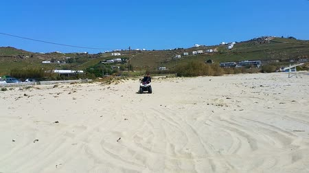 racers : active man having fun and getting extreme ride on quadcycle along sandy beach