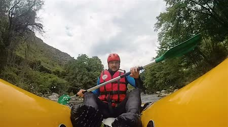 riskli : Male thrill-seeker riding on rough mountain river on his kayak, passing stones