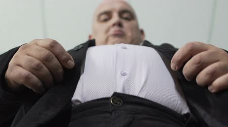 umbigo : Base view of plump man in classic suit fastening a button on his jacket, closeup