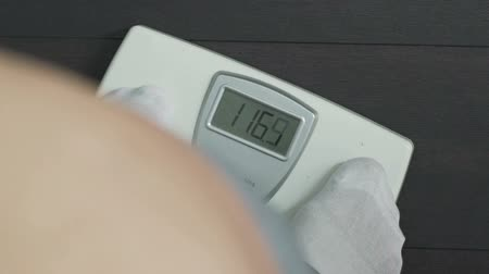pound : Corpulent male stepping on health scales and looking at display, extra weight Stock Footage