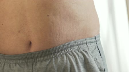 упитанность : Closeup of obese man standing in front of mirror and touching his fat belly