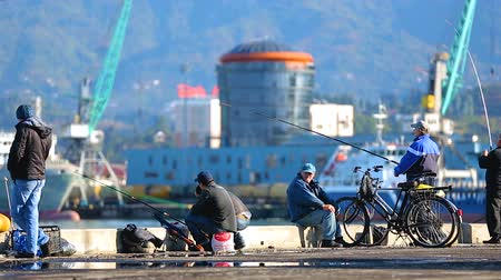 industrial fishing : Adult fishermen enjoying fishing at Batumi port, hobby and leisure activity Stock Footage