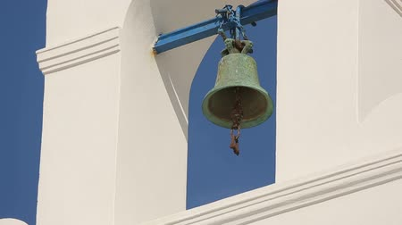 comemoração : Rusty old bell handing in white arch against clear blue sky on sunny summer day