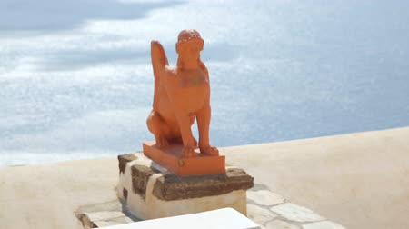 esfinge : Clay statue of Greek sphinx on Santorini island against blue sunlit sea, tourism