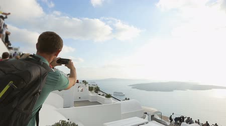 Санторини : Backpacker making video of street performance on Santorini, popular attraction
