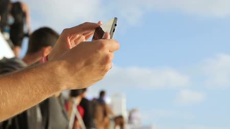 gravado : Man holding smartphone in hands, checking video recorded before, famous festival