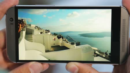 olasılık : Mobile phone screen showing obstacle jumping on Santorini, parkour, slow motion Stok Video