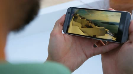 cellphone : Male holding cellphone and watching video of parkour on Santorini, competition Stock Footage