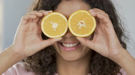 eye piece : Portrait of cheerful biracial woman applying halves of orange to eyes, optimism