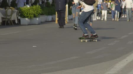 riskantní : Young guy skateboarding along crowded pedestrian route, warm sunny day, slow-mo