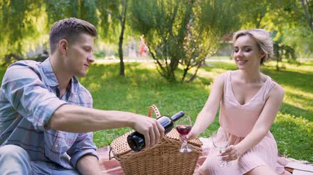 rubi : Man filling glasses with ruby wine and saying toast to beloved, anniversary Stock Footage