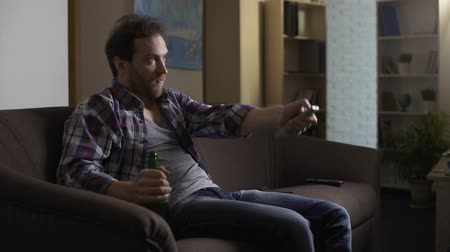 оплаченный : Guy sitting on sofa with beer bottle in hand, using remote control to switch TV