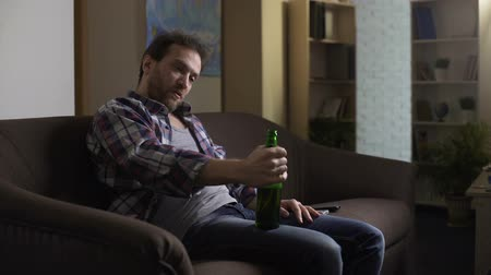 hallucinating : Drunk male sitting on couch and talking to bottle of beer, addiction to alcohol