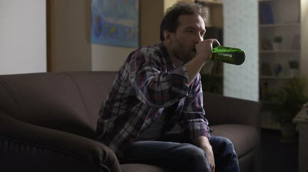 wasted : Drunken man sitting on sofa and looking at beer bottle, having hiccups, alcohol