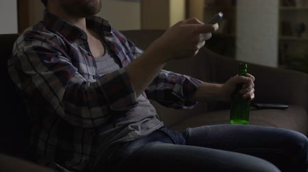 bakalář : Man holding bottle of beer on knee, switching TV channels with remote control