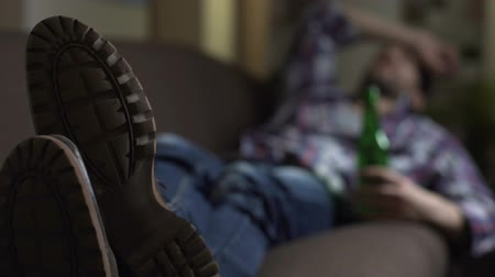 preocupações : Drunk male sleeping on couch with bottle of beer in hand, bad news, emotions Stock Footage