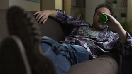 pitiable : Wasted guy lying on sofa, drinking up beer from bottle, dozing off, alcoholism