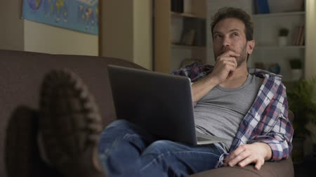 возможность : Adult man sitting on sofa with computer on lap thinking, future plans, choice