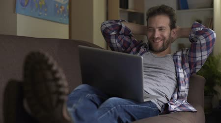 jobless : Tipsy man watching video on laptop, smiling and falling asleep, idle lifestyle