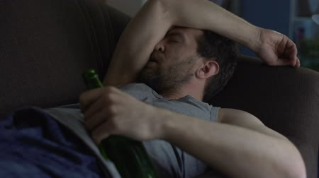 addiction recovery : Wasted guy sleeping on sofa holding bottle of beer in hand, addiction to alcohol