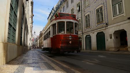 lizbona : Small red tram arriving at stop in order to pick up people, urban transportation