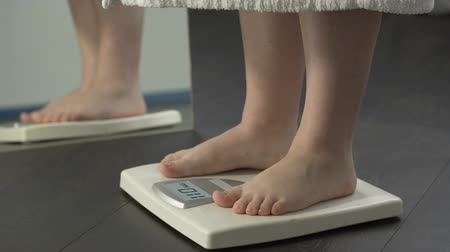 дополнительный : Weight problems, lady stepping on scales at home to check weight, extra fat
