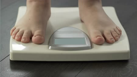 стандарт : Normal weight, woman stepping on scales to check diet results, front view