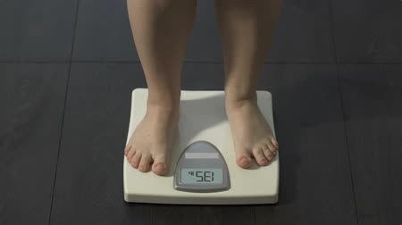 libra : Healthy dieting, girl stepping on bathroom scales to check weight, normal index