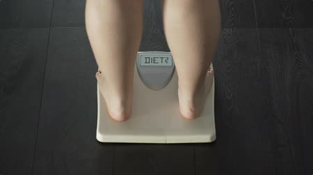 escrito : Female measuring weight, stepping on scales, questioning herself if go on diet