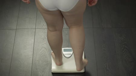 libra : Fat girl measuring body weight on bathroom scales, problems with overeating