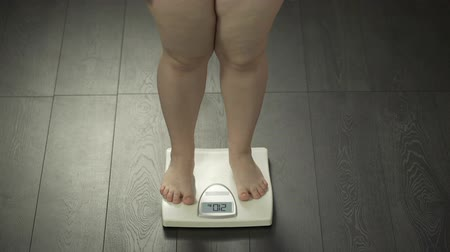 libra : Female with extra weight stepping on bathroom scales, health disorder, obesity Vídeos