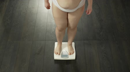 libra : Woman stepping on bathroom scales to measure weight, unsuccessful diet, failure