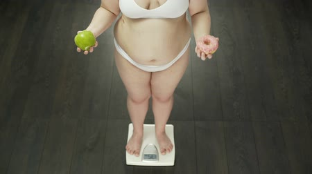 kobliha : Chubby woman standing on scales with apple and donut, choosing sweets, nutrition Dostupné videozáznamy